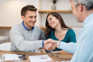 Молодая пара получает документы на дом